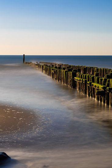 Golfbreker aan het strand in het water.
