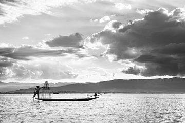 Zwart-wit foto van een visser met zijn visnetten op de boot op het Inle meer in Myanmar van Twan Bankers