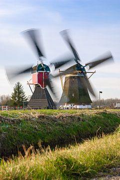 Zwei historische holländische Mühlen im Wind von Michel Geluk