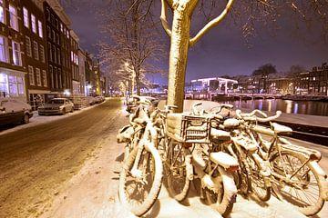 Besneeuwd Amsterdam bij nacht aan de Amstel van Nisangha Masselink