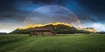 Bergen bij zonsondergang met regenboog