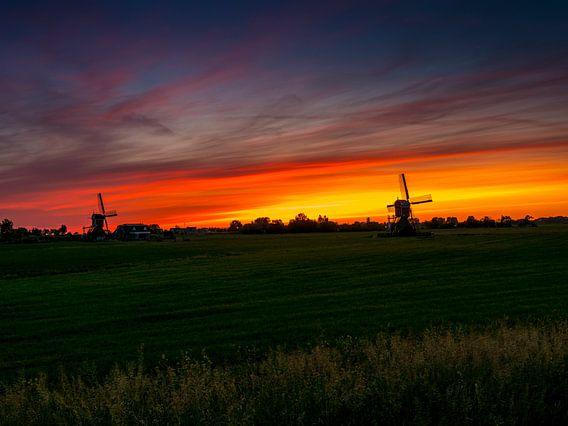 twee windmolens bij zonsopgang in Nederland.