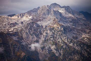 Hoher schwerer Steinberg (felsiger Berg) ragt in Wolkenstücken auf, raue Schönheit. von Michael Semenov