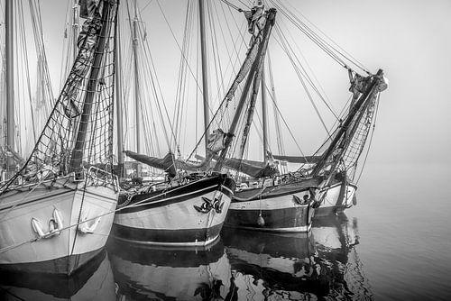 Oude zeilschepen in de mist aan de kade van Kampen