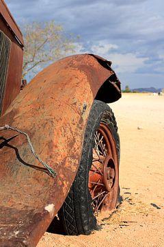 Oude verroeste en verlaten oldtimer autowrak in de woestijn van Bobsphotography
