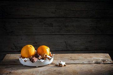 kerstkoekjes en sinaasappels in een kom op een rustieke tafel, donkere houten achtergrond met een gr van Maren Winter