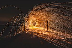 Rondvliegende vuurspetters van staalwol op een brug in de nacht.