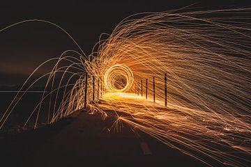 Rondvliegende vuurspetters van staalwol op een brug in de nacht. van Fotografiecor .nl