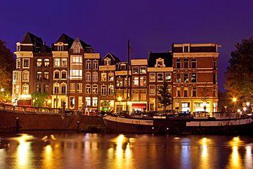 Traditionele middeleeuwse huizen aan de Amstel in Amsterdam bij nacht van