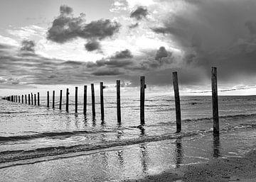 Strand zwart-wit palen in zee, dreigende lucht van Marjolein van Middelkoop