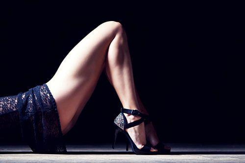 Benen van een vrouw liggend op haar rug in lingerie van