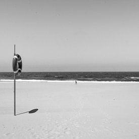 Eenzaam figuur op een verlaten strand van Reis Genie