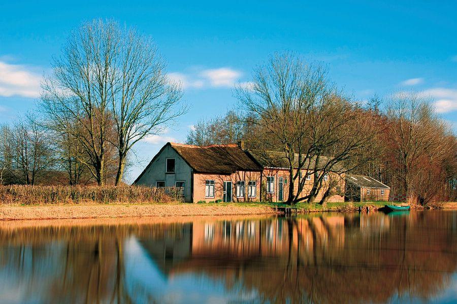 Oud huisje gespiegeld in het water van de boezem