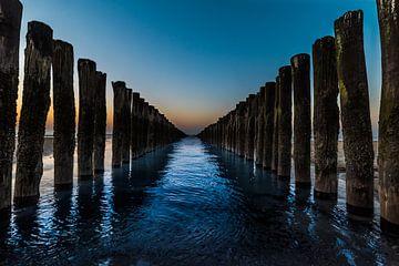 Golfbrekers bij zonsondergang in Domburg ( symmetrie ) van Marjolijn van den Berg