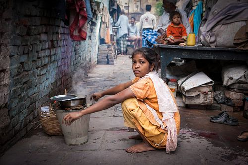 Indiaas meisje doet de afwas in de achterbuurt straten van Varanasi  in India. Wout Kok One2expose van
