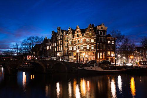 Verlichte grachtenpanden in de schemering in Amsterdam van
