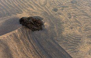 Vulkanische rots en zand patronen in het water van