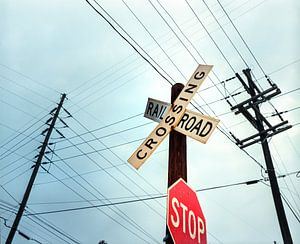 Old Midwest railroad warning crossing sign and stop sign at dawn