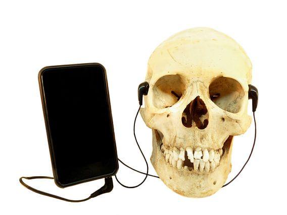 Menselijke schedel luistert muziek met oordopjes op een iPod
