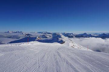 Skipiste in Kitzbühel, Tirol (Österreich), umgeben von Berggipfeln und Wolken von Kelly Alblas