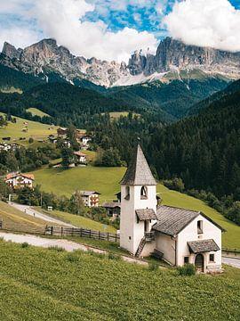 Kerk in de Italiaanse dolomieten met de ruige bergen in de wolken op de achtergrond. van Michiel Dros