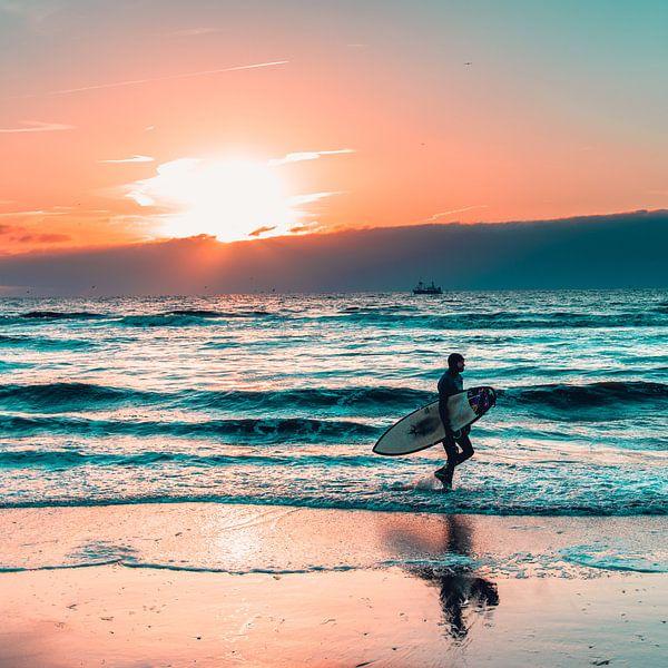 Surfer op het strand van Scheveningen met zonsondergang van Wahid Fayumzadah