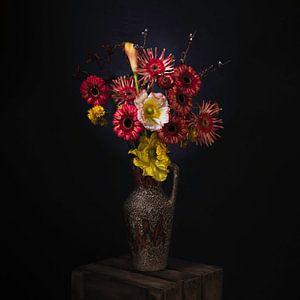Malerisches Stilleben von roten und gelben Blumen in einer Retro-Vase.