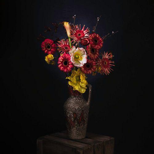 Schilderachtig stilleven van rode en gele bloemen in een retro vaas.