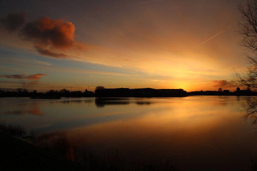 Zonsopkomst met oranje wolken die reflecteren op het water van de Hollandsche IJssel bij Moordrecht van André Muller