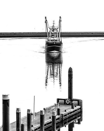 Visserskotter vaart de haven van Harlingen binnen in spiegelend water.