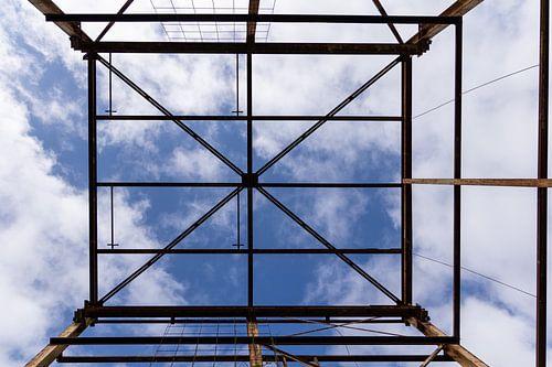 Urbex symmetrie- verroeste metalen constructie tegen een blauwe lucht met wolken