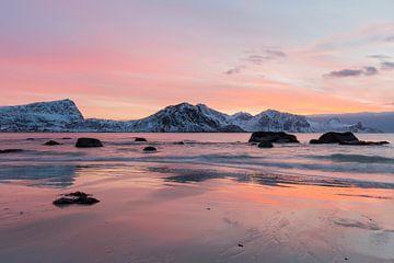 Der Sonnenuntergang hüllt das Meer und einen Strand mit Felsen in einen orangefarbenen Schein. von Sander Groffen