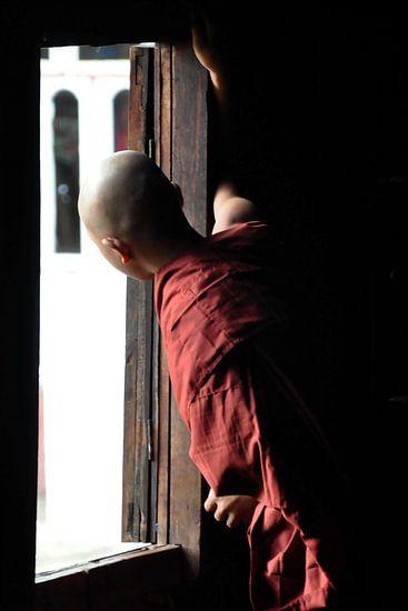 Monnik kijkt naar buiten vanuit zijn houten klooster van Shwe Yaunghwe