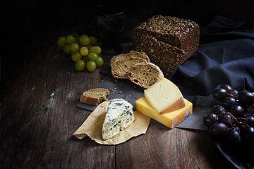 rustieke maaltijd met diverse kaas, volkorenbrood en druiven op een donkere houten tafel, kopieerrui van Maren Winter