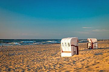 Strandkörbe stehen im Sonnenuntergang auf einem Badestrand an der Ostsee mit Meer und klarem Himmel von