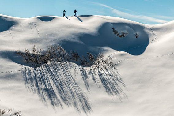 Winterwandelaars op een maagdelijk witte heuvelrug in Oostenrijk