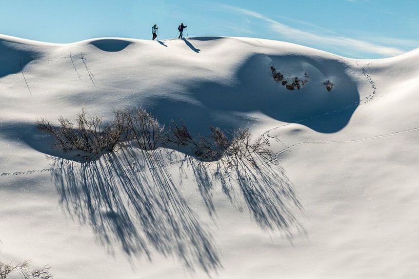 Winterwandelaars op een maagdelijk witte heuvelrug in Oostenrijk van Jonathan Vandevoorde