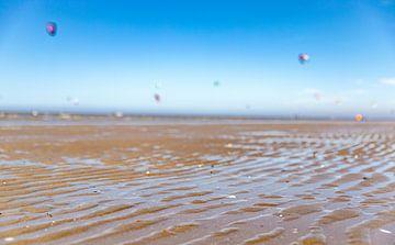 Close-up nat zand met kitesurfers van Percy's fotografie