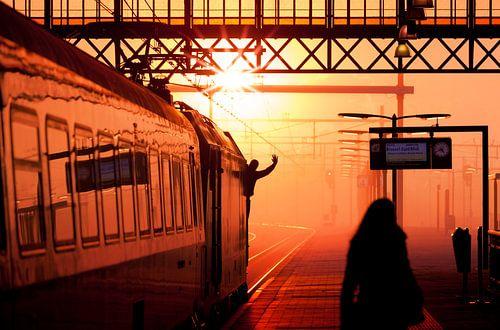 Silhouette van trein machinist die vertreksein geeft tijdens zonsondergang