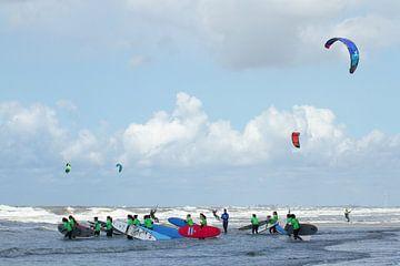 Kleurige surfplanken, kitesurfers en surfkleding bij les in de branding bij Zandvoort aan Zee van Suzan Baars