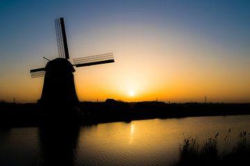 Silhouet van molen aan het water bij ondergaande zon van Sander de Vries