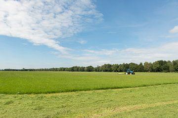weiland maaien met blauwe tractor en maaimachine van Tonko Oosterink