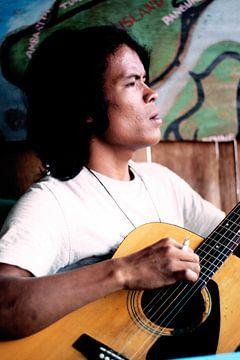 Indonesische jongen speelt gitaar I van André van Bel