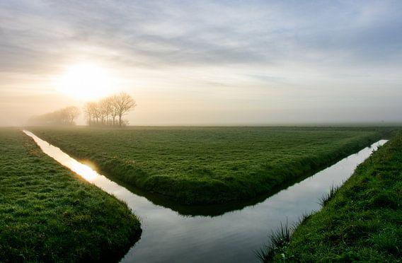 Uitgestrektheid van een  Hollandse polderlandschap tijdens zonsopkomstt
