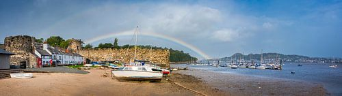 Regenboog boven het strand en de stadsmuren van Conwy, Wales