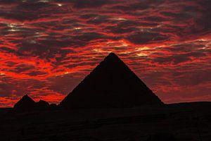 De dramatische zonsondergang achter een van de 3 grote Pyramides in Cairo - Egypte