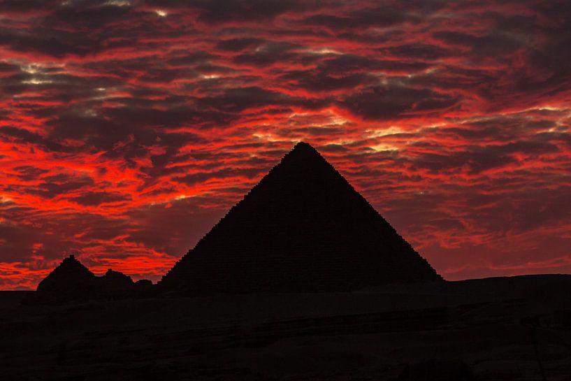 De dramatische zonsondergang achter een van de 3 grote Pyramides in Cairo - Egypte van Michiel Ton