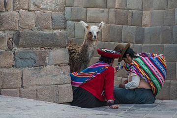 Twee Peruaanse vrouwen met lama bij een oude Incamuur van Rietje Bulthuis