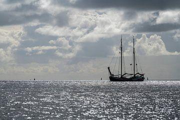 Zeilboot tegen de schittering van de zon in de Waddenzee nabij het eiland Terschelling van Tonko Oosterink
