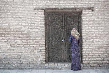 Femme priant près d'un bâtiment en pierre avec une porte en bois | Turkménistan